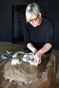 Zoe Gudovic works on her mask at the Macanudos Workshop